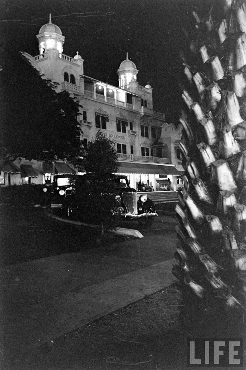 """Here is a wonderfully atmospheric shot of the Hollywood Hotel captured by a Life magazine photographer in 1936. Interestingly the hotel's sign across the front reads """"HOTEL HOLLYWOOD"""" rather than the other way around. On my website, I have another photo taken that same night from the other side of the driveway: https://wp.me/p5XK3w-3bK"""