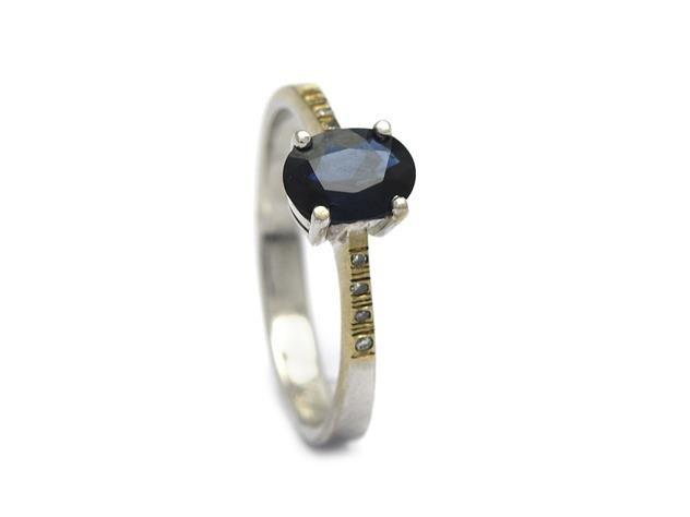 RING, 18K vitguld, blå safir ca 0,80 ct, 8 briljanter ca 0,04 ctv, stl 17,5 mm, vikt 3,1 g.