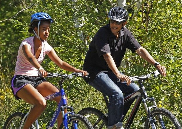 U.S. President Barack Obama rides alongside his daughter Malia during their family vacation on Martha's Vineyard in Massachusetts in this August 23, 2011 file photo. Both Obama and Republican Mitt Romney are likely to spend little of the summer in...