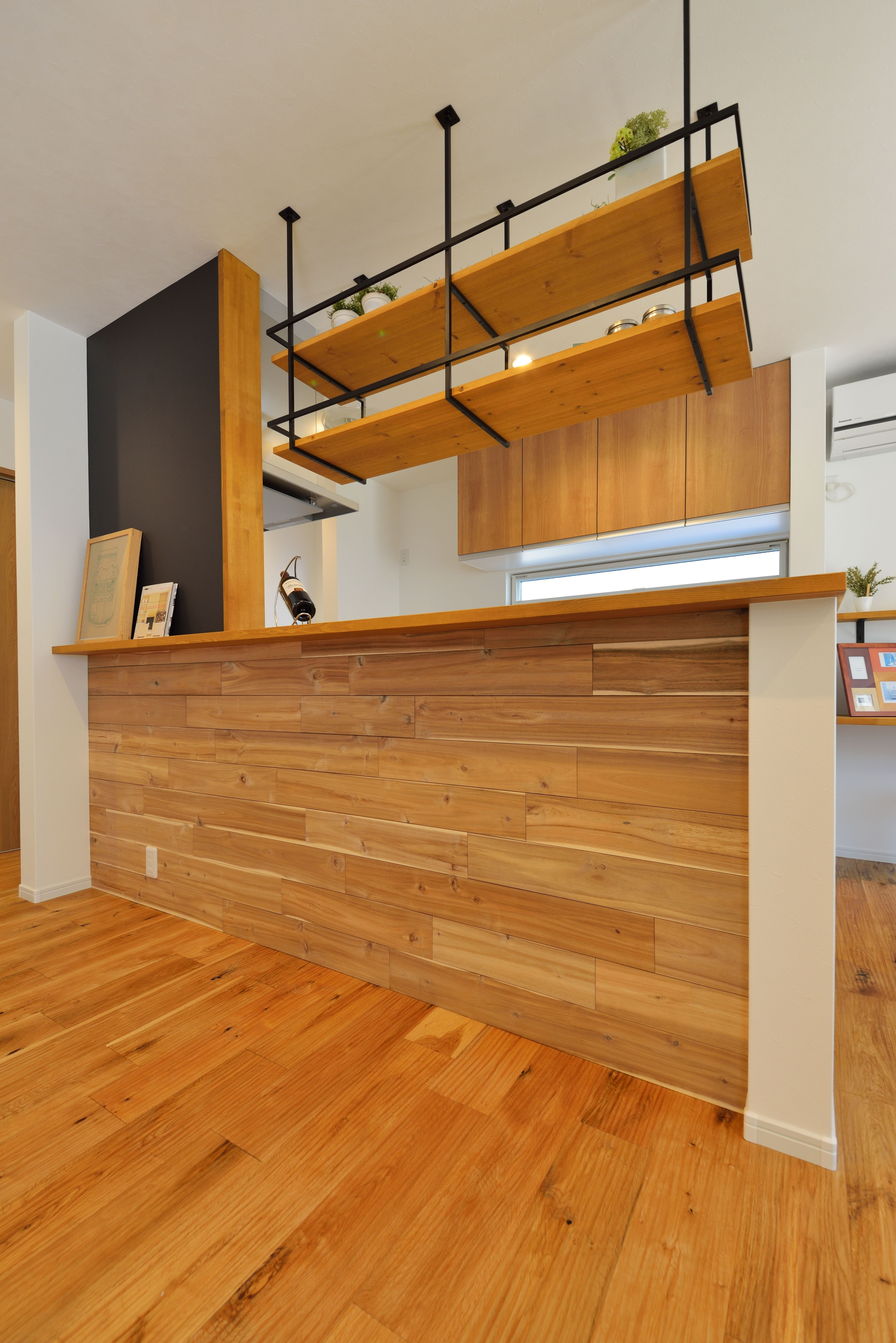 キッチン 腰壁には ホワイトウォールナット の羽目板でアクセント 上部に設けた吊り棚はアイアンの強さと素材の美しさが際立つオリジナルのデザイン キッチン アイアン