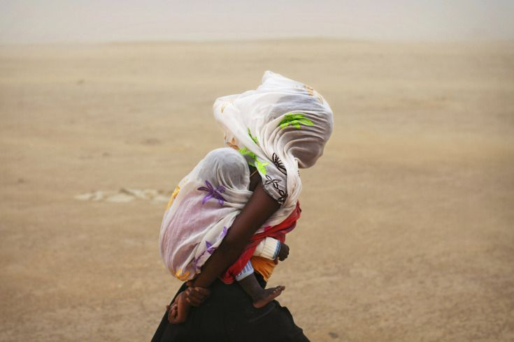 Joe Penny / Reuters - July 29, 2013. A woman carrying her baby and wrapped with a shawl walks through a sandstorm in Timbuktu.