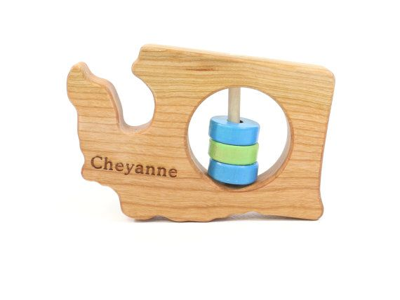 Modern Baby Rattle – Cherry Washington State Rattle™  What a great modern gift to give as a keepsake! An organic, all natural wooden rattle in the shape of the sate of Washington. As your baby plays, they develop their senses of touch, sight, and sound. Makes a fun and personal gift. Listing is for one rattle.  •Specifications:  -Size: approximately 3.5x4 inches – perfect shape for a babies grip and has built in grasping spots.  -Finished with a light coating of natural beeswax and flaxseed…
