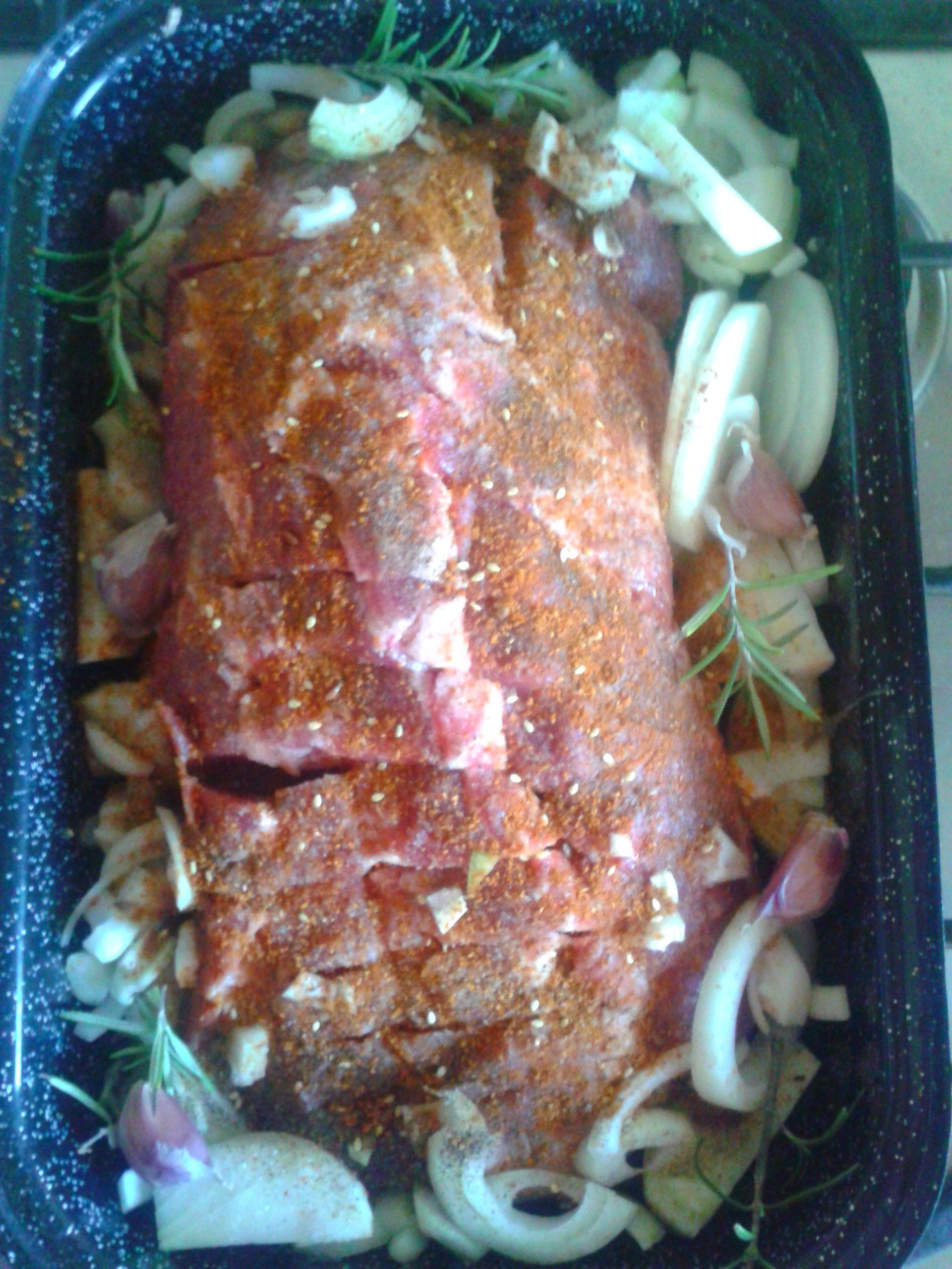 bravčová krkovička pripravená na pečene s cesnakom, cibuľou, rozmarínom, posypaná zmesou zo soli, čierneho korenia a údenej červenej papriky.