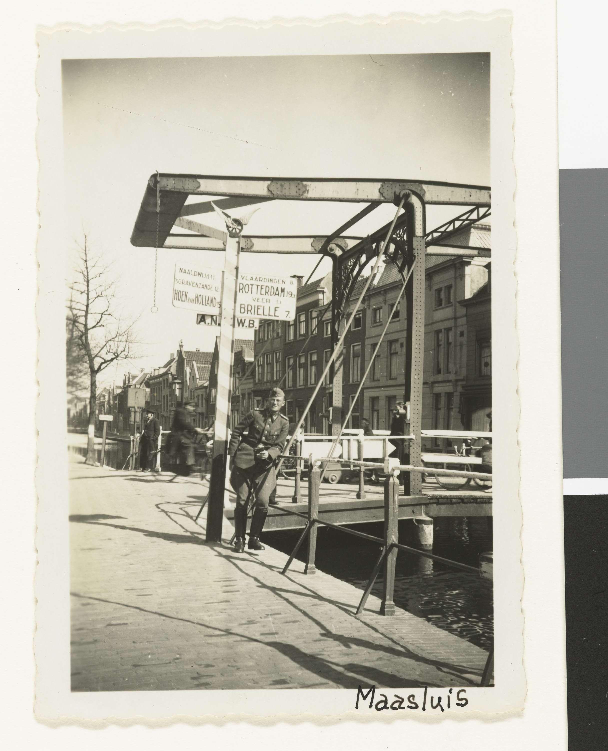 Anonymous | Duitse soldaat poseert bij ophaalbrug, Anonymous, 1940 - 1943 | Een Duitse soldaat poseert voor de foto tegen de railing langs een gracht bij een ophaalbrug in Maassluis. Hij draagt een legerpet en in zijn hand houdt hij een camera. Achter hem huizen en voetgangers en een ANWB bord dat de richting aangeeft naar: Naaldwijk, s'Gravenhage , Hoek van Holland, Vlaardingen, Rotterdam en Brielle. (zelfde man als op NG-2007-5-35 t/m 38)