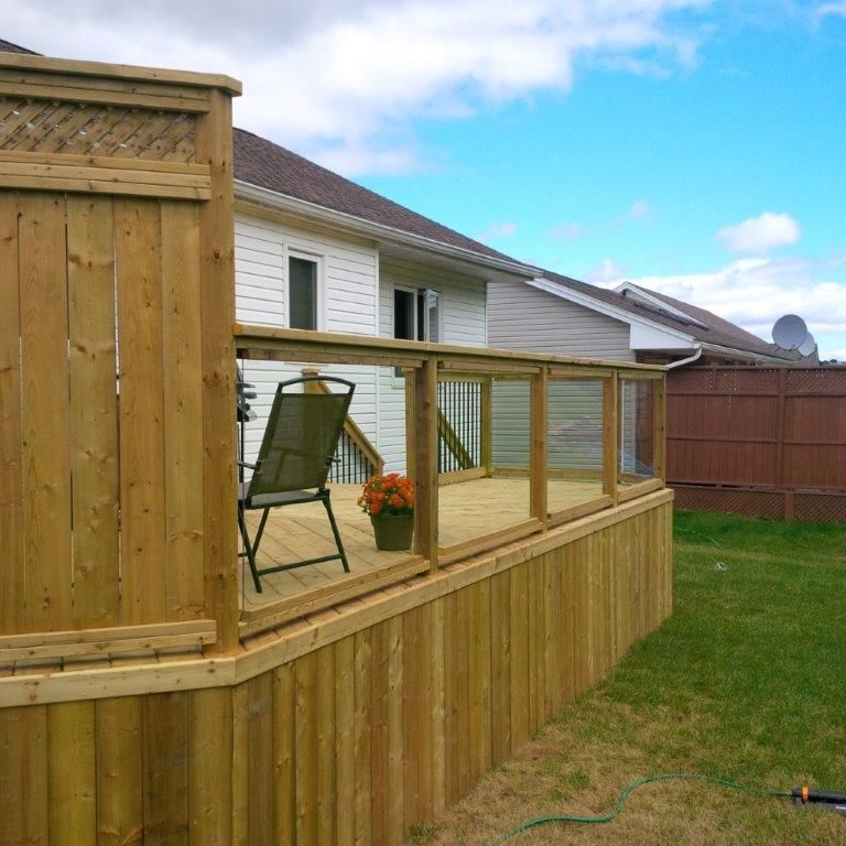 Pressure Treated Lumber With A Tempered Glass Railing Deck