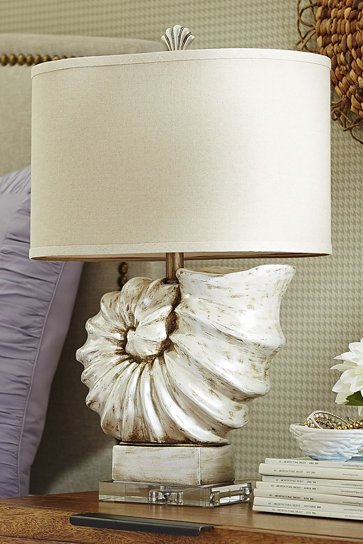 Flaunting A Luxurious Champagne Luster Finish And Topped By An Ivory Linen Shade And Shell Finial The Nautilus Lamp From Pier 1 M Beach House Decor Beach Cottage Decor Coastal Decorating
