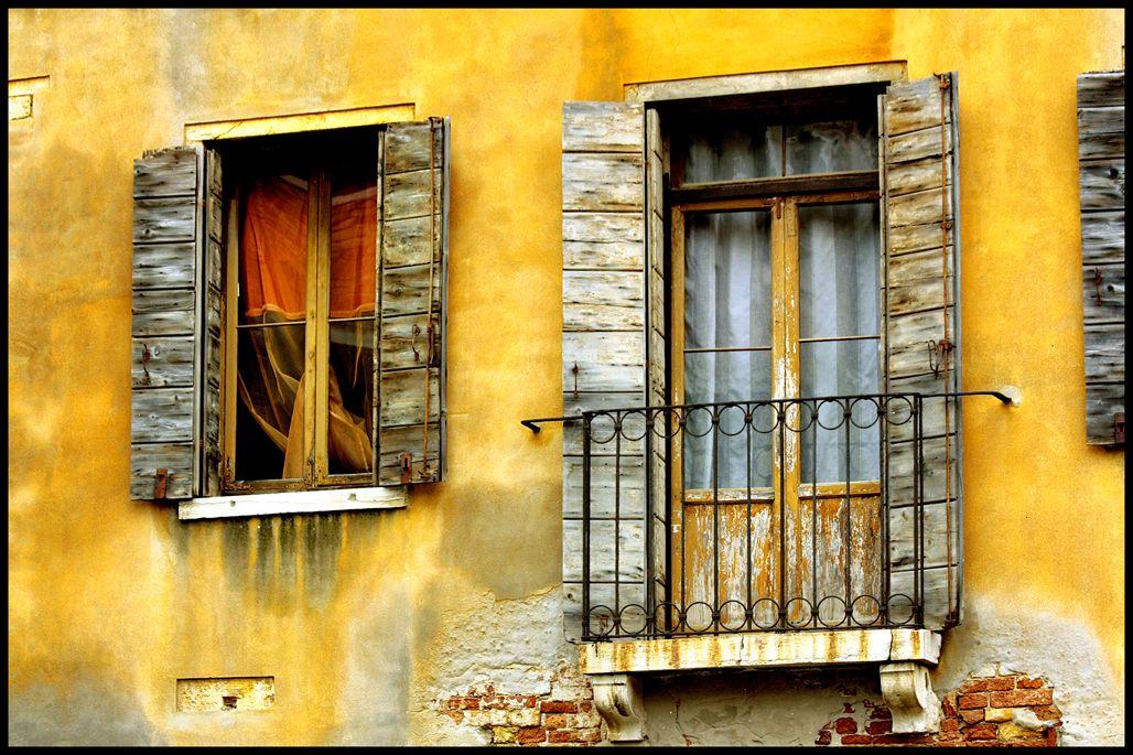 Window and balcony on yellow wall