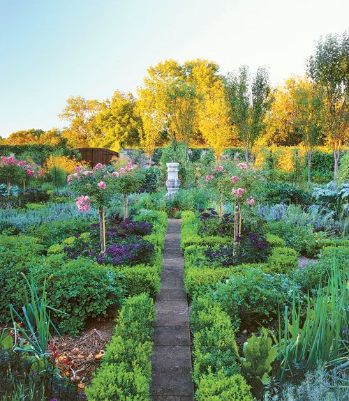 Flowers are sprinkled throughout this Connecticut garden, from the bold prelude—a moody row of rose and clematis arbors—to herb beds anchored in 'Fairy' rose standards rising above fragrant heliotrope. The homeowner also devoted ample space for purple basil beside sweet, jalapeno, and paprika peppers.   - CountryLiving.com