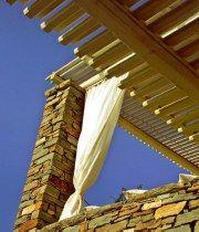 Σήμα κατατεθέν στον εξωτερικό χώρο του σπιτιού, που σχεδίασε και κατασκεύασε ο αρχιτέκτονας Κώστας Μπέρδος, τα αλλεπάλληλα σκιάδια από παράλληλες τάβλες και οι αέρινες κουρτίνες.