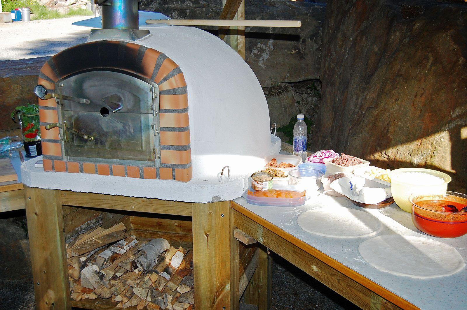 Ulkokeittiö Kälviällä. Cozzin kiviuunin ympärille on rakennettu tasot leipomista varten. Pieni puuvarasto uunin alapuolella helpottaa uunin lämmitystä.