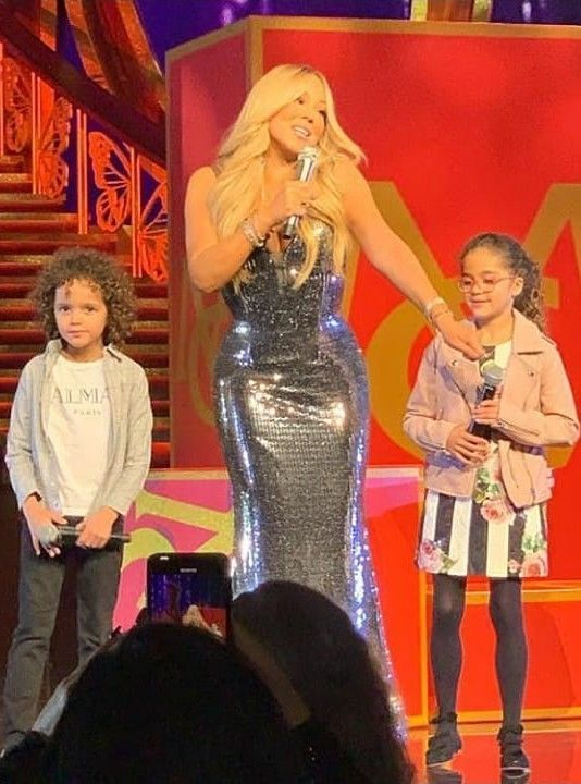 Cuties! Mariah Carey with her twins on stage during her concert. Love the outfit worn my Mariah's daughter Monroe Cannon! This gorgeous DOLCE & GABBANA Girls Mini-Me Rose Black Stripe Sun Dress is from the Spring Summer 2018. Inspired by the Women's Love Christmas Collection, Monroe looks adorable wearing this pretty sundress made in fine cotton and has a pink rose and black stripe print.Twin brother Morocco wore a trendy Balmain white t-shirt. #mariahcarey #demkids #dolcegabbana #celebirtykids