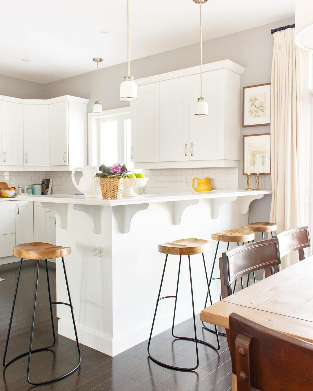 White kitchen with quartz counters and wooden barstools for the