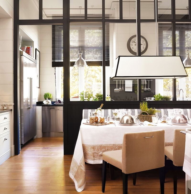 A Modern Black And White Kitchen Dining Room Combination Has Glass Partition To Visually Separate The Work Spaces From Area