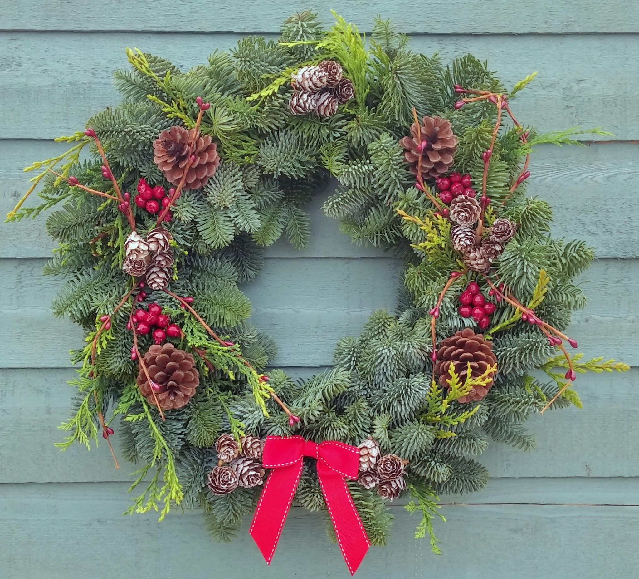 The homemade Natural Wreath is decorated with pine cones