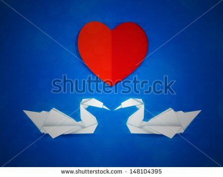 Two white paper swans and red heart on blue background.