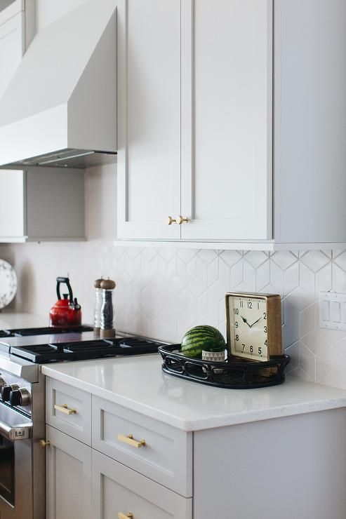 White geometric backsplash tiles complement light gray shaker cabinets adorned with brass knobs and fitted on either side of a light gray vent hood. #graycabinets