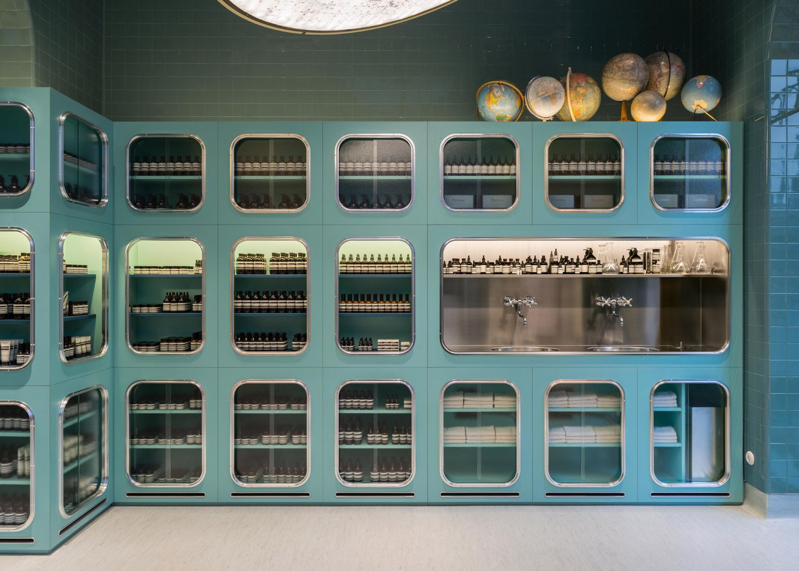 dimorestudio designs glossy teal interior for aesop store
