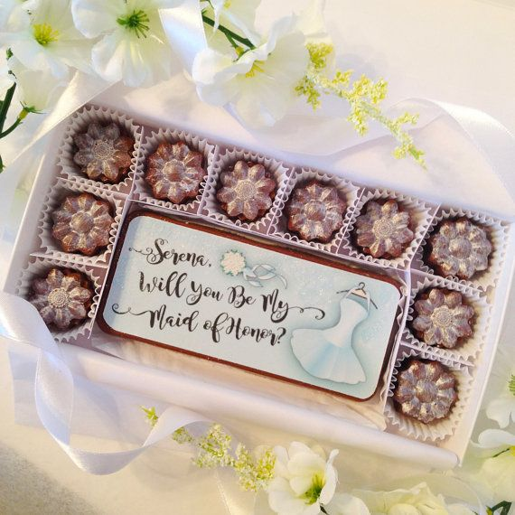 Will You Be My Maid of Honor Chocolates. Personalized Maid of Honor proposal. A unique and beautiful way to ask your best friend to be at your side. Colorful edible design, personalized with your maid of honor's name, even has sparkling sugar bling. Includes 10 flower shaped chocolates with a silver glow and one large chocolate bar. By DiamondChocolates