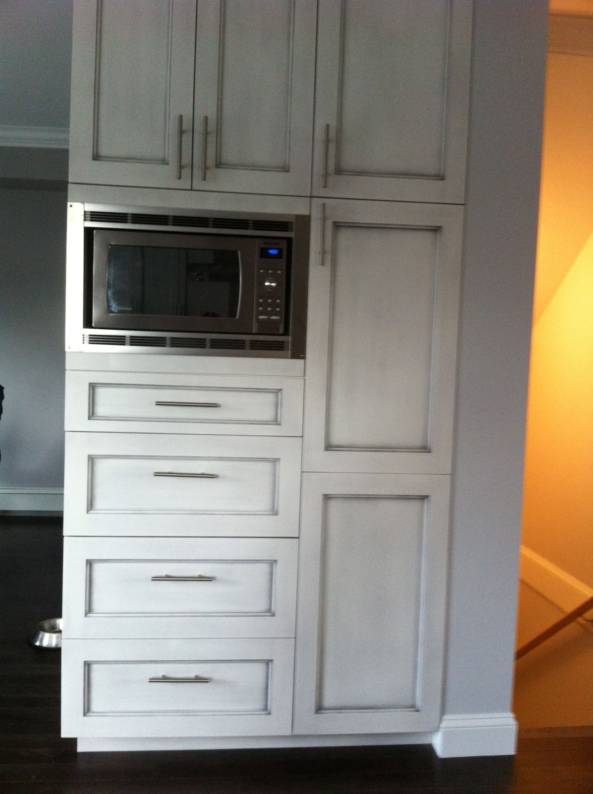 custom pantry with built in microwave and antique brushed cabinets