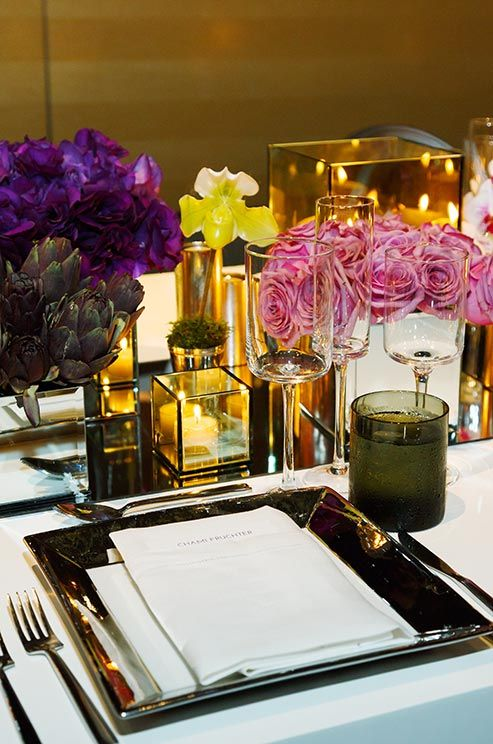 Classic pink roses and deep purple lisianthus are mixed with unexpected purple artichokes and individual lady slipper orchids.