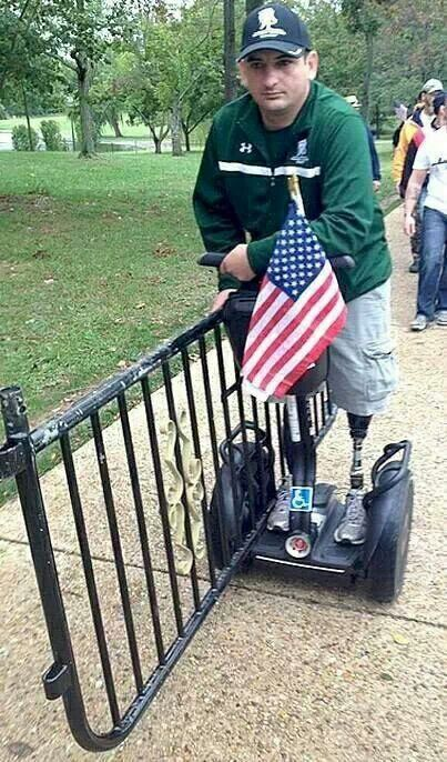 Double amputee carrying barricade from memorial-The heart,dedication,pride and willingness,this Vet has is inspiring and humbling. Once again he is fighting for  America this time against his own President!  Our Vets sang Christian songs and said the Pledge of Allegiance w/ Flags flying! THIS IS WHAT AMERICA REALLY LOOKS LIKE!