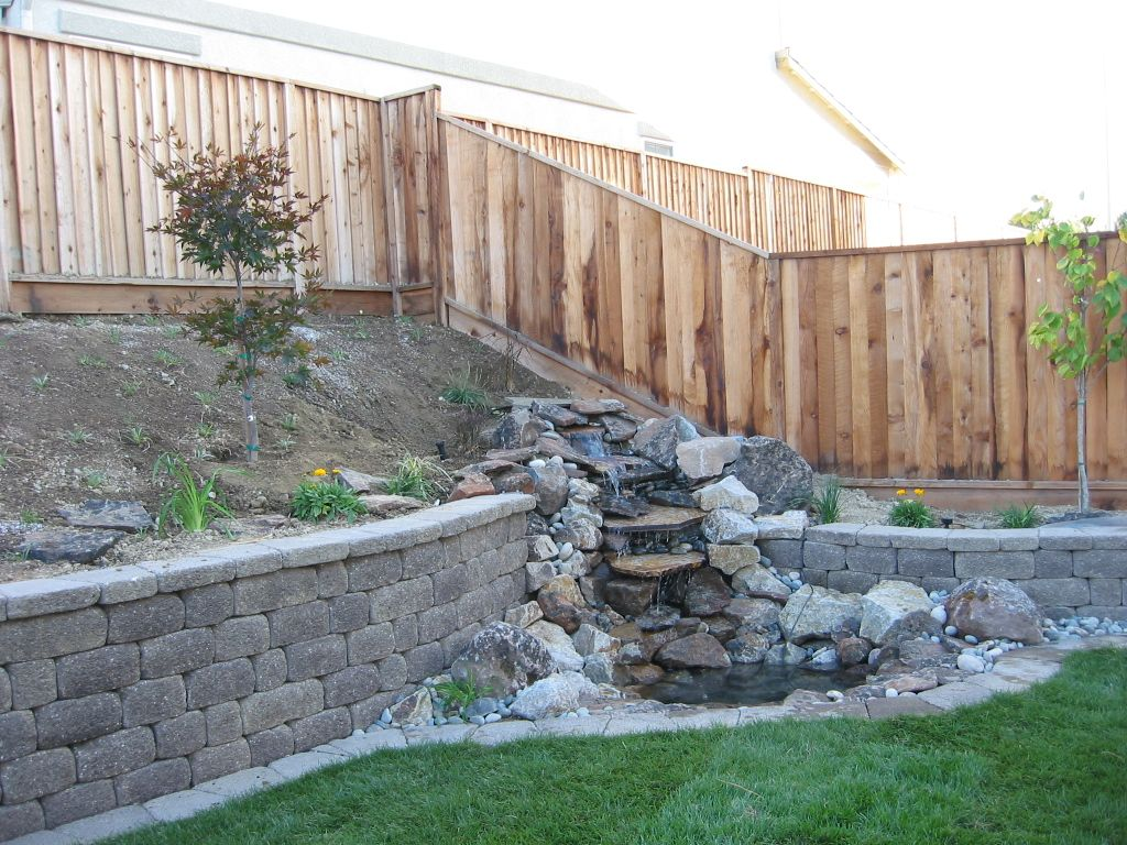 water feature integrated into retaining wall  though the wall should be made with more natural