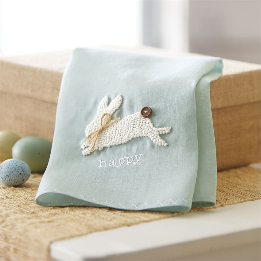 """Artfully hand-knotted French knot bunny with wood ?button tail and jute twine bow ?around neck features """"happy"""" ?embroidery and cross-stitched hem on gray-blue linen towel.?"""