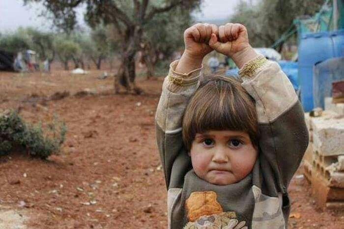 A little kid in Siria surrounding to a camara. Niño en Siria se rinde al ver la camara pensando que era un arma de fuego.