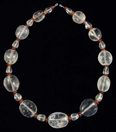 """ROMAN ROCK CRYSTAL AND CARNELIAN BEAD NECKLACE           I-II century A.D.   Composed of eleven scaraboid shaped rock crystal beads, twelve biconical rock crystal beads. Interspersed with twenty-four biconvex carnelian beads. L. 18 1/4"""" (46.4 cm)."""