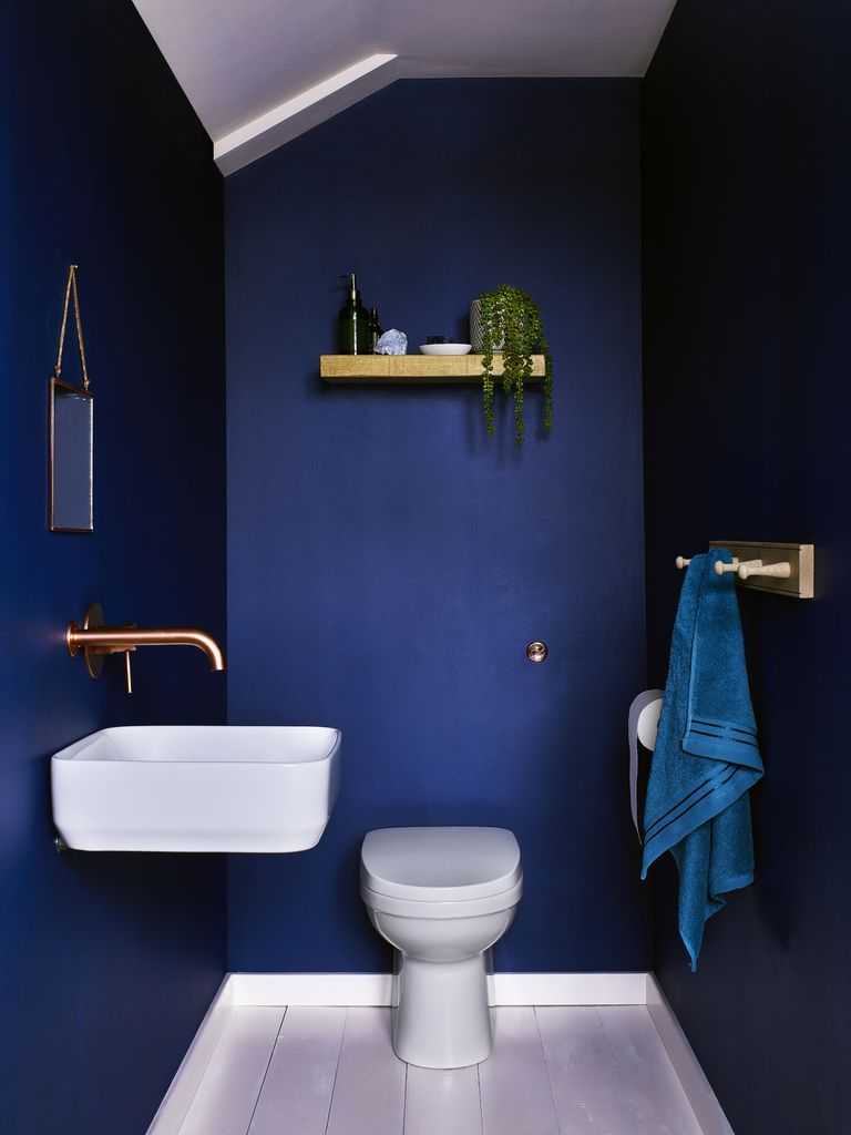Dulux's Sapphire Salute is a deep and rich dark blue. Seen here in a small downstairs toilet/cloakroom, Sapphire Salute was voted the most popular paint colour for the bathroom, according to a study by luxury online bathroom retailer Drench. The metallic gold accents add a luxe feel while the wood shelving and towel rack calms the space. (Photo: Dulux)