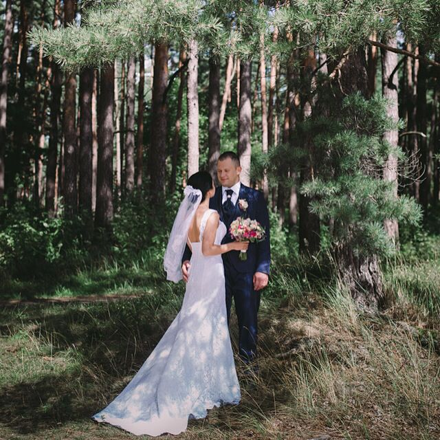 Wedding Photoshoot in forest. Lace Wedding dress for bride and gorgeous groom in dark blue suit.