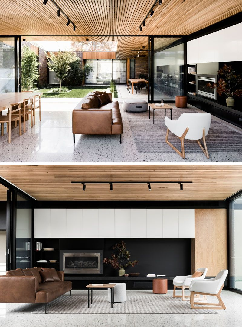 Inside this modern house a timber batten ceiling contrasts the white concrete floor keeping the interiors light and and airy a black wall in the living