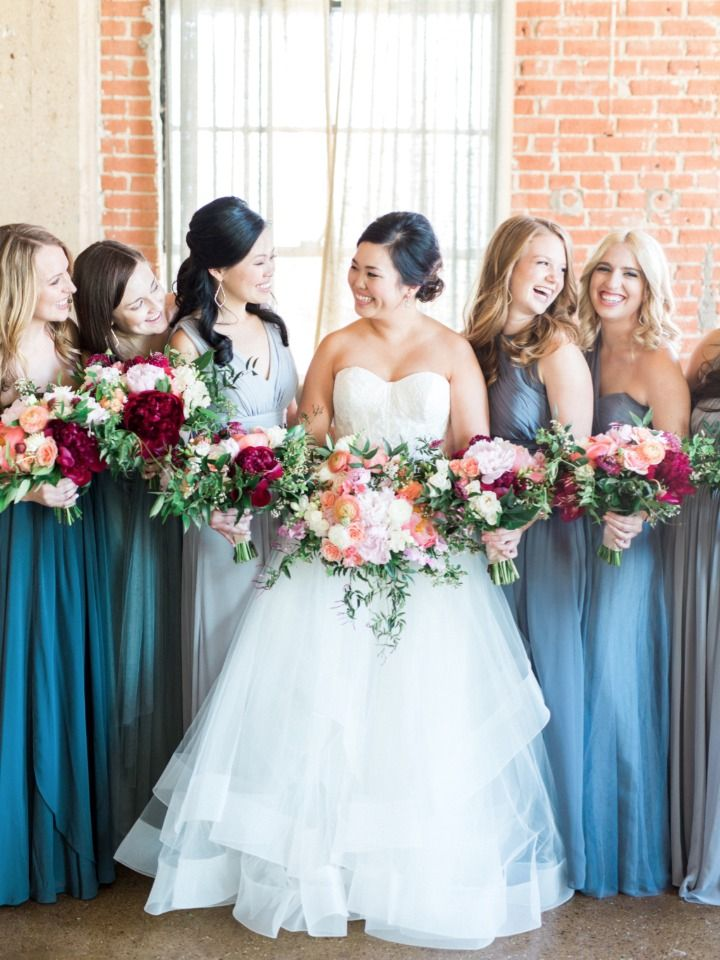 b9823b0167 bridesmaids in assorted blue dresses with peach and deep red bouquets