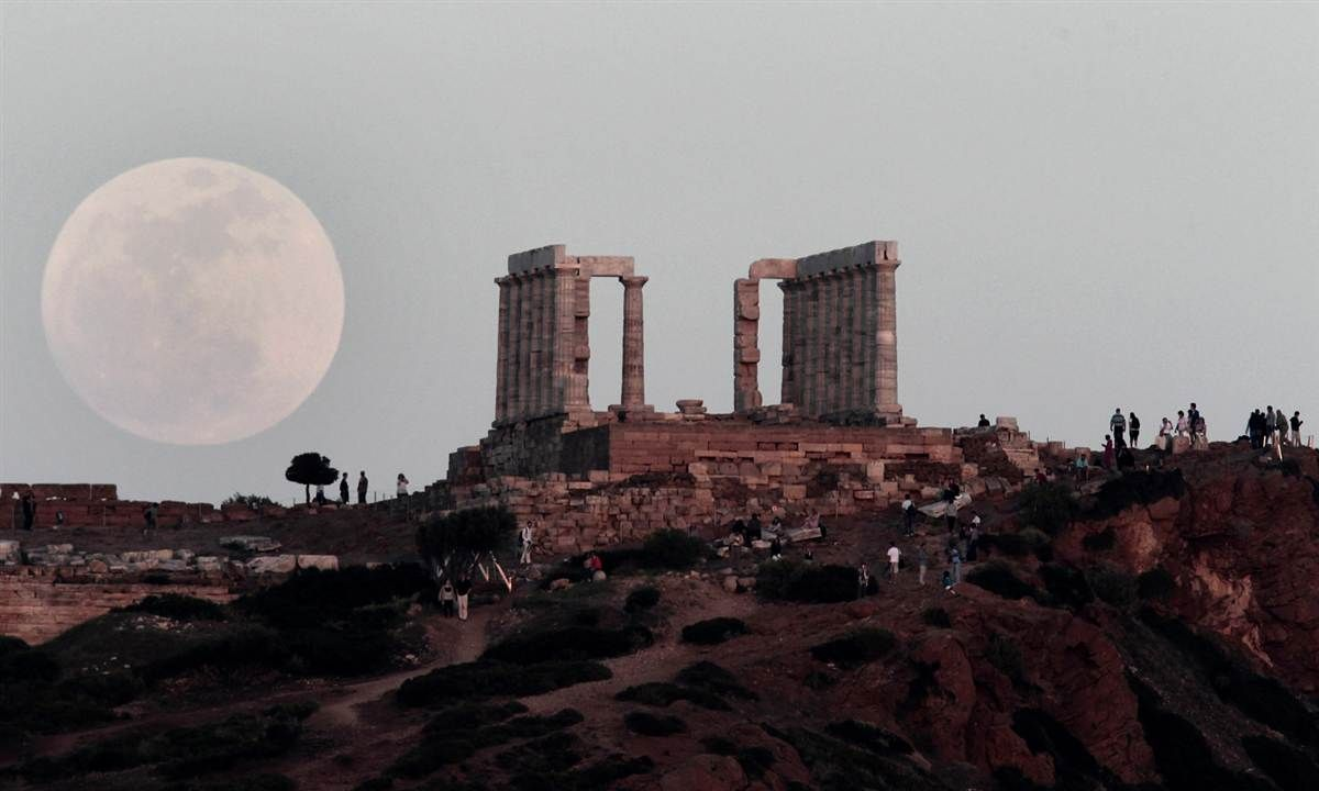 Ancient evening. The full moon rises behind the Greek Temple of Poseidon in Cape Sounion, southeast of Athens, while tourists watch on May 5.