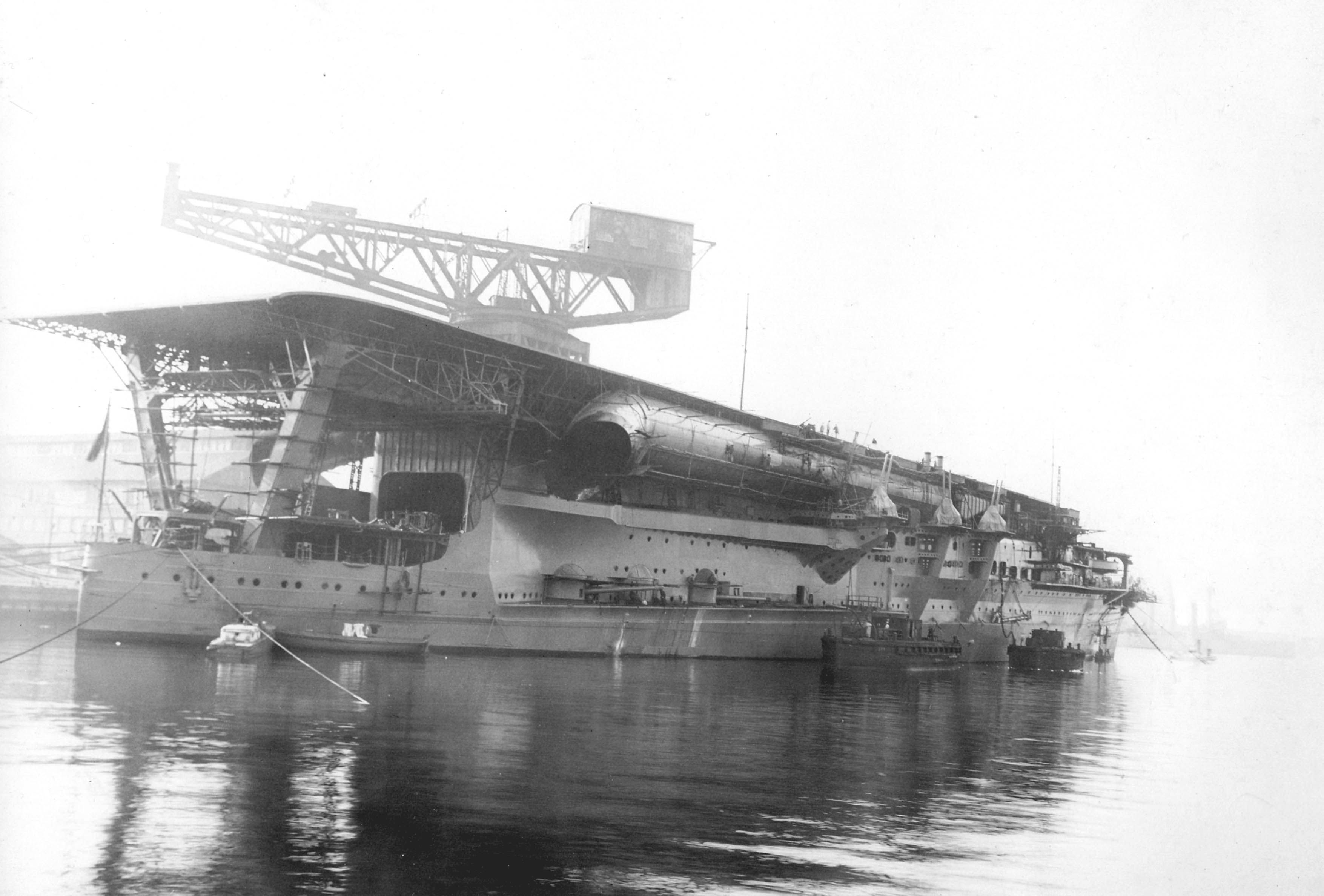 Japanese Navy Aircraft Carrier Kaga being fitted out in 1928. Note the long funnel below the flight deck and the three 8-inch guns in casemates