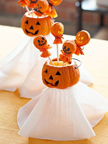 Ghostly Delights Tissue-paper circles embellished with punched shapes turn store-bought suckers into merry jack-o'-lanterns. For a ghostly effect, display them in a mini pumpkin container resting on top of an upside-down glass covered with cheesecloth.