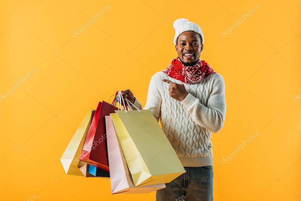 African American Man Winter Outfit Holding Shopping Bags Pointing Finger In 2020 Winter Outfits Men African American Men Winter Outfits