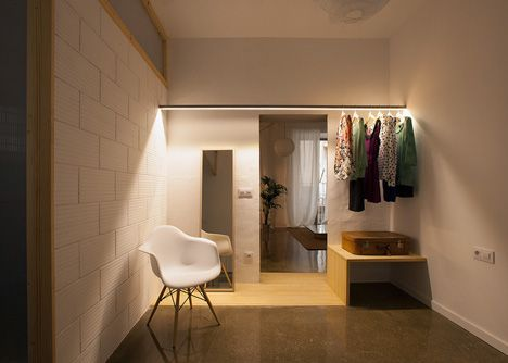 Genial garderobe - lampe integreret i bøjlestang.  Bemærk trægulvet deler huset i nat og dag zone og bliver til en bænk. Twin House by Nook Architects