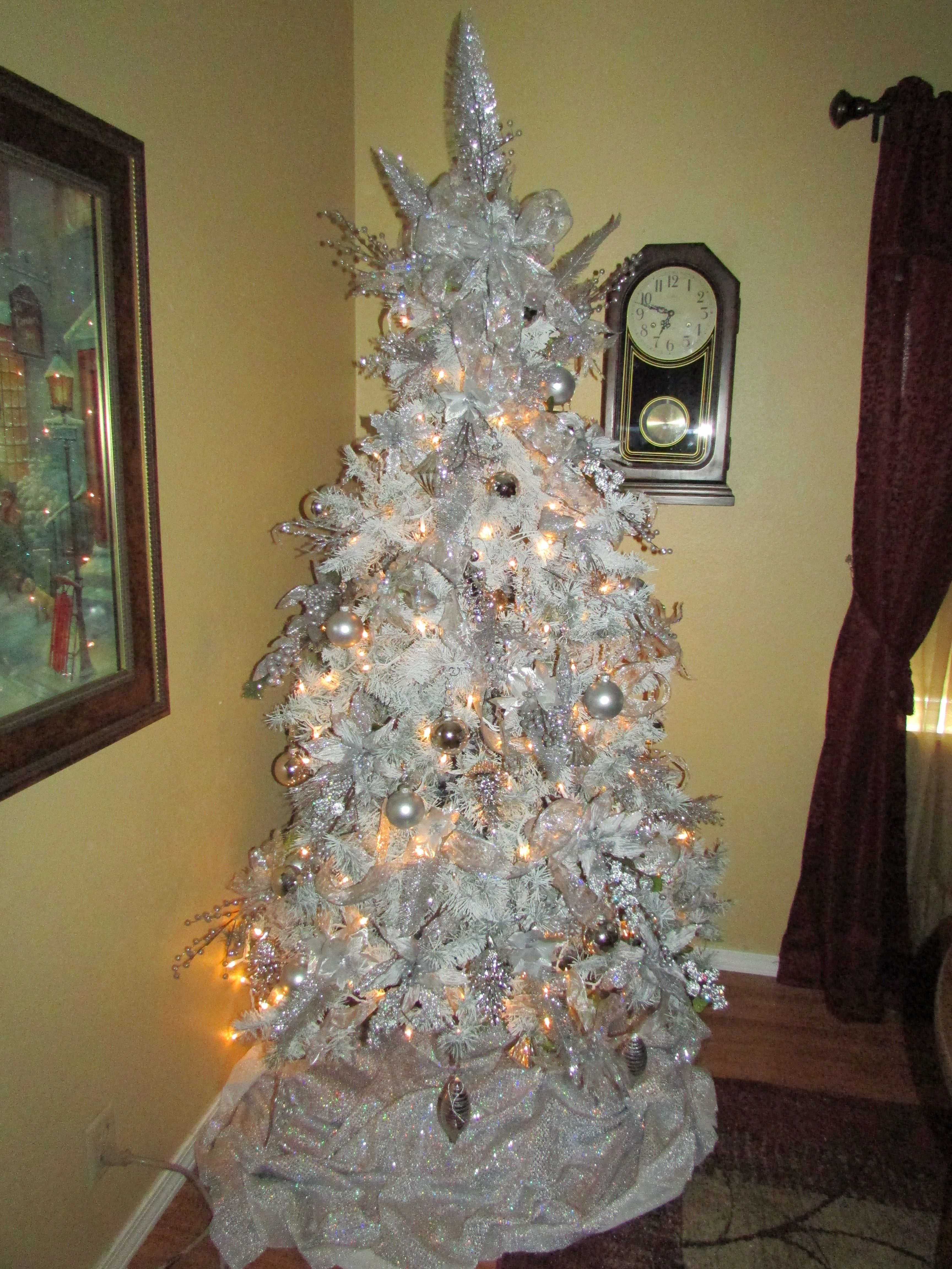 Flocked a green artificial Christmas tree using white