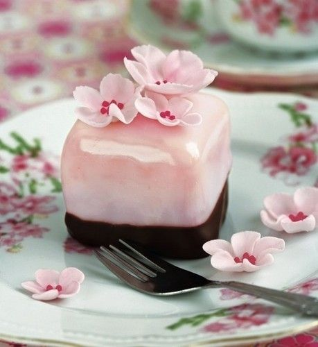 Pink petit four garnished with pink flowers dipped in chocolate