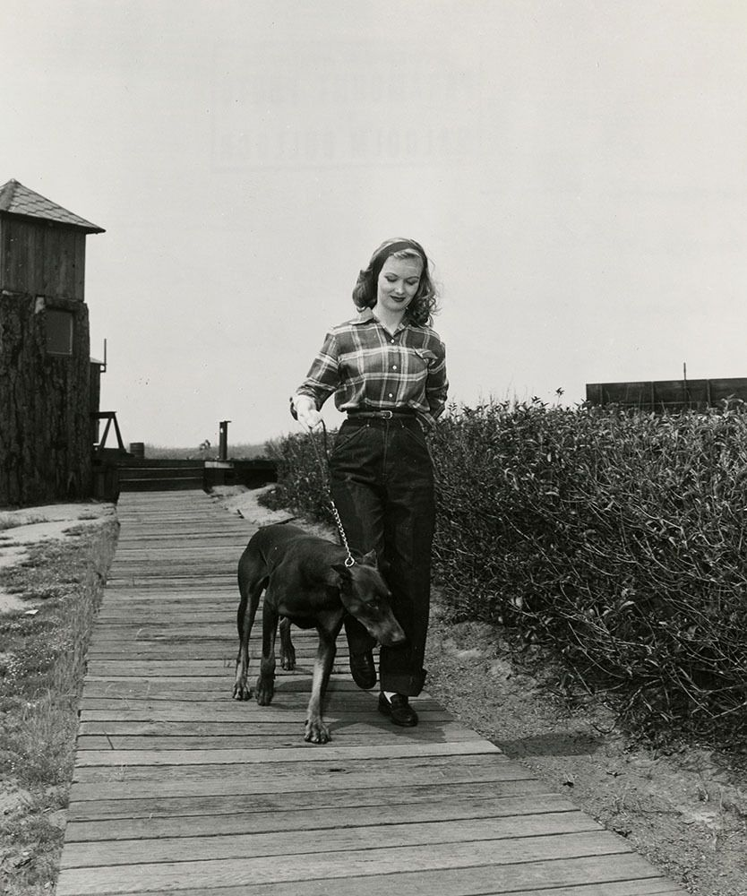 Veronica Lake walking her dog at her home at the