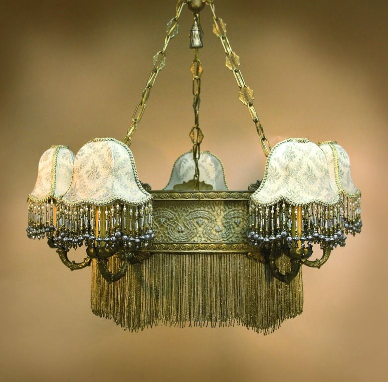 Antique Chandelier. Mini Gish shaped shades extend on ornate brass arms from a central ring chandelier. The shades are a pale caramel silk with a fine silver lace overlay and beaded fringe. The ornate metal ring is also covered with a soft gold silk, then overlaid with gold and silver metallic laces. From its bottom edge hangs dyed silk and beaded fringe.