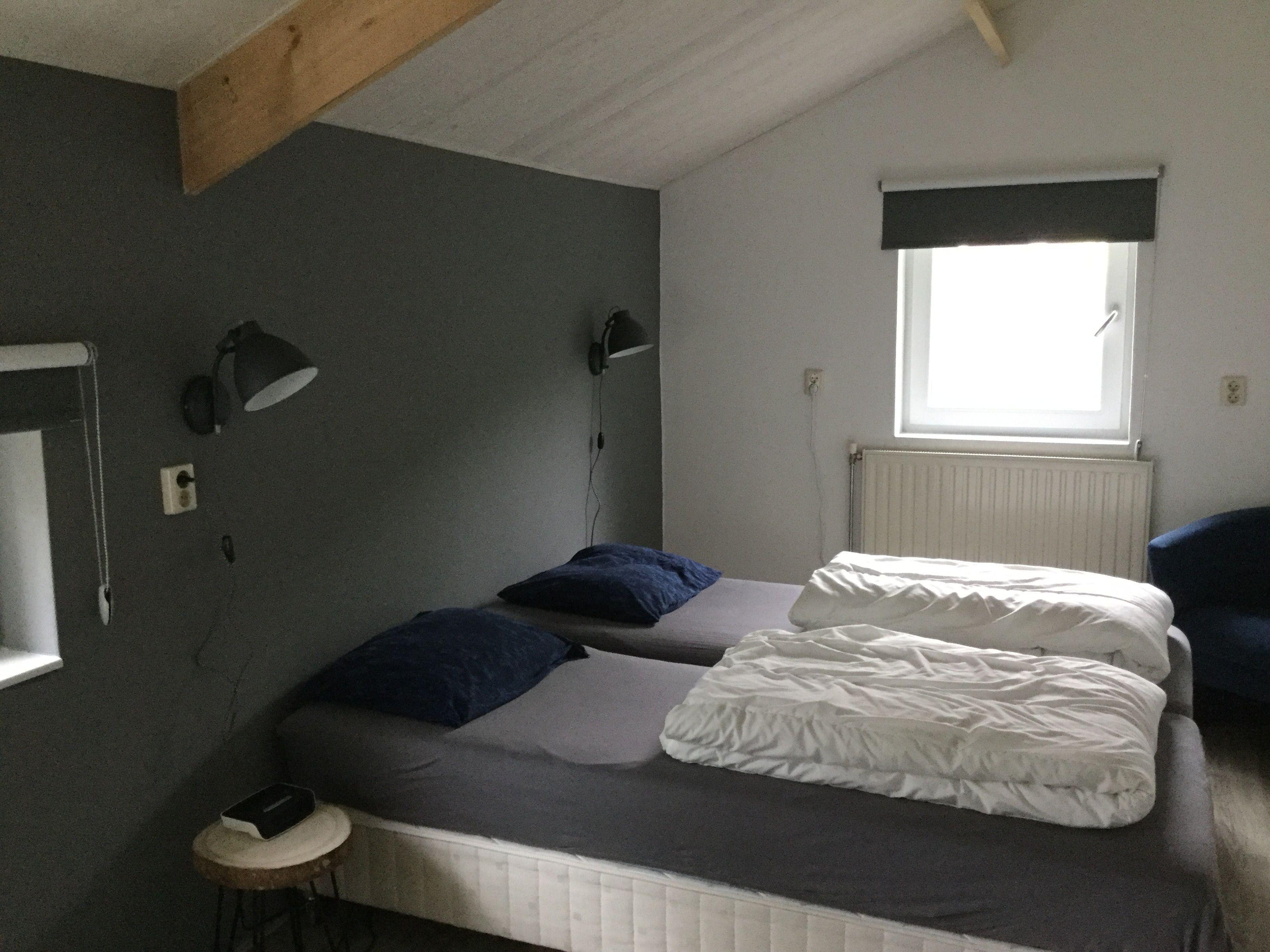 Slaapkamer met houten plafond en balken en stoere wandlampen ...