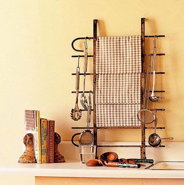 Sweet idea for vintage lovers!    Shop flea markets and architectural salvage stores to find objects you can repurpose for distinctive storage. This piece of wrought-iron garden fencing stands on its end on the counter and holds dish towels and cooking tools.    Beside it, cast-iron tub legs serve as bookends to keep cookbooks upright.