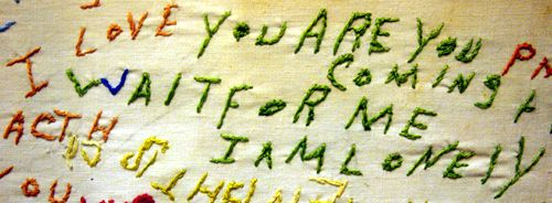 """Cloth embroidered by a schizophrenic patient.  This portion includes the phrases, """"I love you,"""" """"are you coming,"""" """"wait for me,"""" and """"I am l..."""