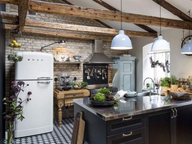 Открытые шлифованные деревянные балки стропильной системы делают помещение выше и создают атмосферу сельской кухни.