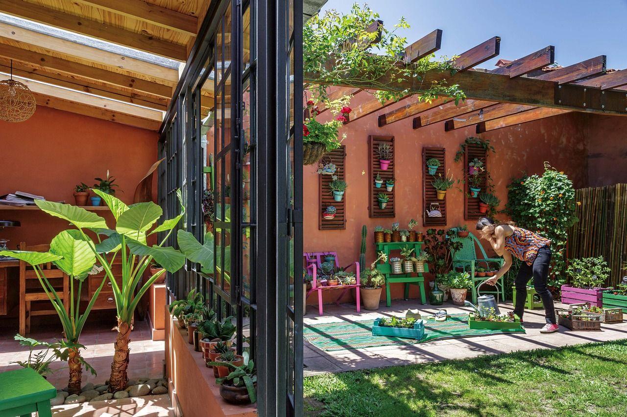 patio rstico en terracota con toques de color verde y violeta con cerramiento en vidrio