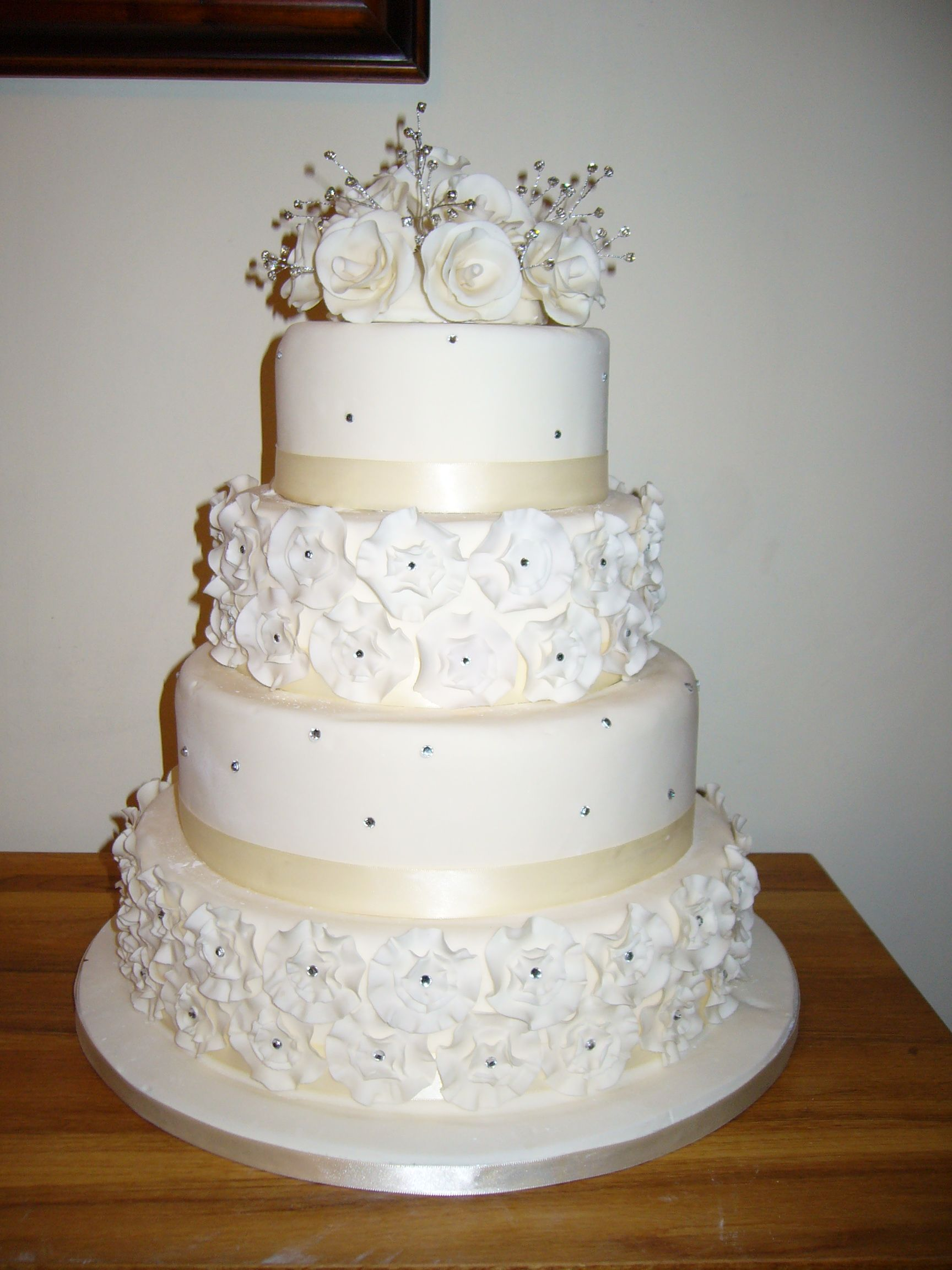 Large four tier ivory wedding cake with sugar rosette ruffles and ...