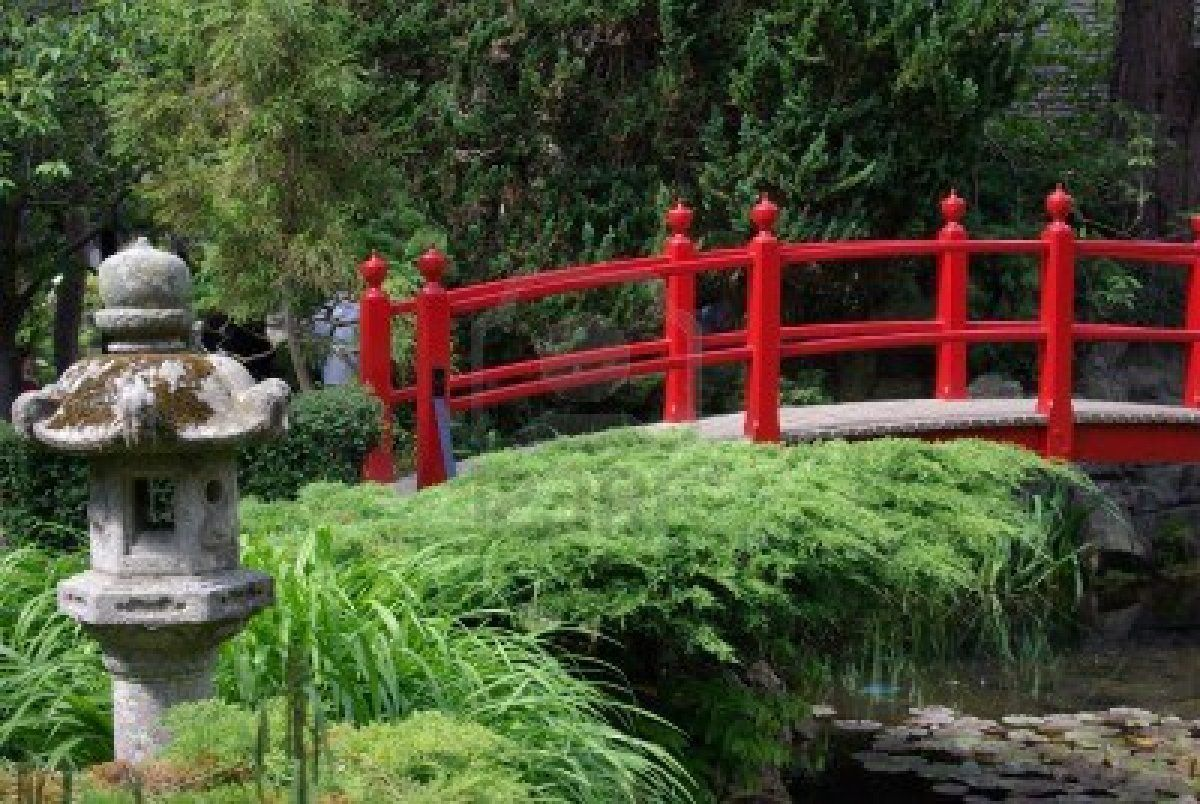 a red bridge in a japanese garden in ireland