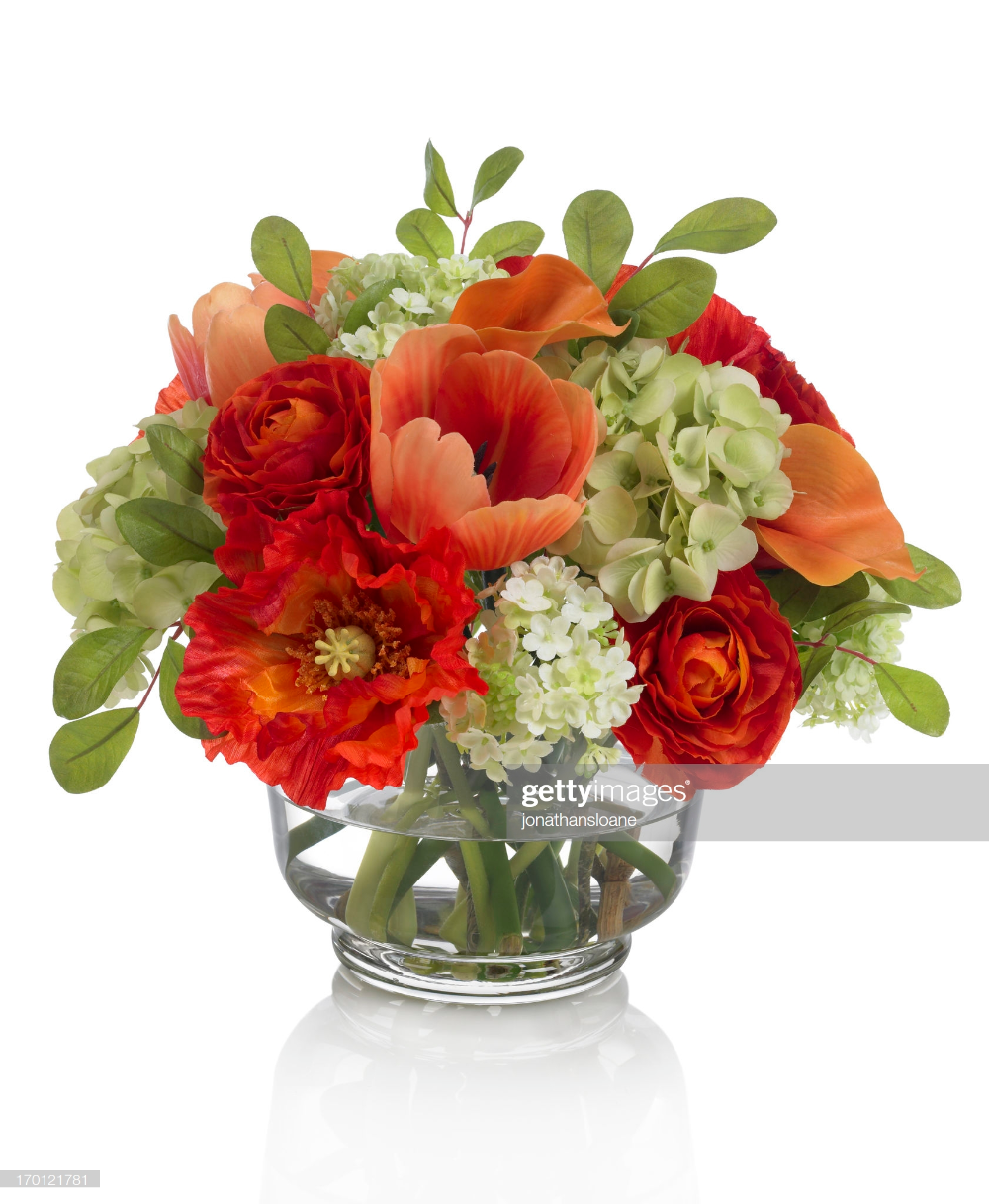 A mixed fall bouquet with tulips and ranunculus in a glass